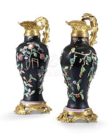 A PAIR OF UNUSUAL CHINESE FAMILLE ROSE BLACK-GROUND RELIEF-MOULDED VASES, MOUNTED IN ORMOLU AS EWERS