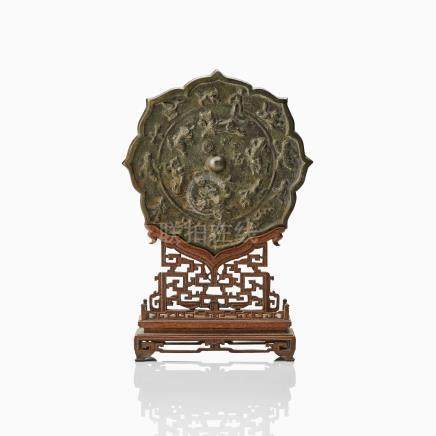 A BRONZE MIRROR IN A CARVED STAND