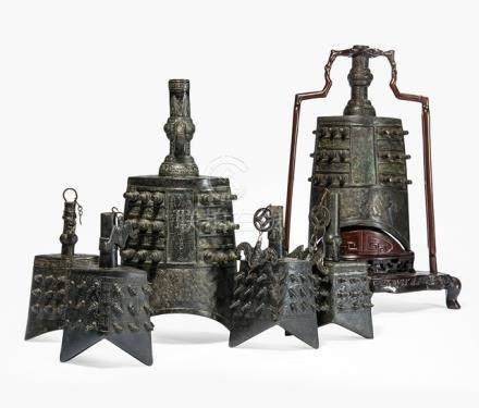 A GROUP OF SIX BRONZE BELLS IN ARCHAIC STYLE, China, Qing dynasty, one with craved hardwood stand - Provenance: Property from an old diplomat collection, assembled in China prior to 1970 - Minor wear, very slightly chipped