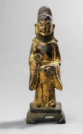 A GILT- AND BLACK-LACQUERED BRONZE FIGURE OF AN OFFICIAL, CHINA, 17th ct., standing on a rectangular pedestal, both hands holding pencil and scroll, wearing various garments, his face displaying a severe expression, beard and his head topped with a hat - Property from an old Dutch private collection, assembled from 1950 till the 1990s, by descent to the present owner - Minor wear