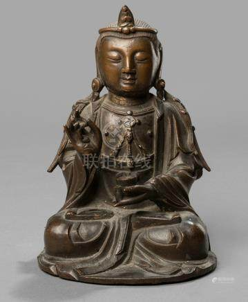 A BRONZE FIGURE OF A GUANYIN, China, ca. 18th ct. Seated in vajrasana, the left hand holding an alms bowl, his hair in two plaits falling over his shoulders, the face with a serene expression - Property from a South German private collection, assembled in the 1990s - Remnants of gilding, minor wear