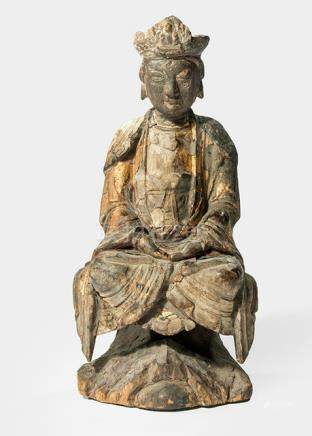 A WOOD FIGURE OF GUANYIN, CHINA, 17th/18th ct., seated in vajrasana on a rock formation with both hands resting in dhyanamudra on her lap, wearing various garments including a wide-sleeved mantle and her face is displaying a serene expression, traces of gilt-lacquer - Property from a German private collection, assembled in the 1970s and 80s - Minor damage due to age