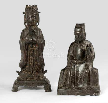 A STANDING AND A SEATED DAOIST OFFICIAL, China, 17th ct., the first bronze standing with booted feet on a shaped pedestal with both hands in front of the abdomen holding a scepter, wearing various garments including a long-sleeved mantle, his face with slit eyes and his head topped with the specific hat secured with a pin, traces of gilt and red lacquer - Property from a South German estate since at least 1985 in the property of the family - Wear, losses
