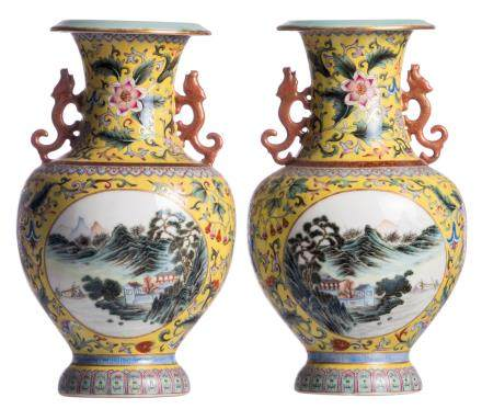 A pair of Chinese yellow ground polychrome and floral decorated vases, the roundels with mountainous river landscapes, the handles dragon relief decorated, with a Qianlong mark, H 31,5 cm