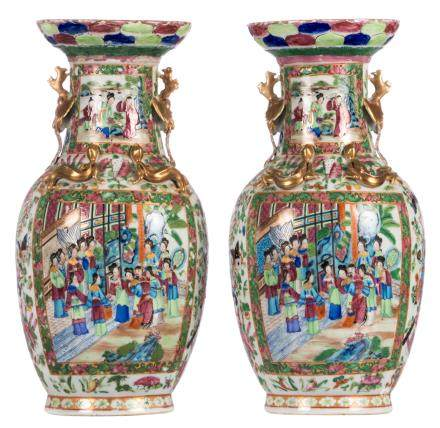 A pair of Chinese famille rose vases, floral and relief decorated, the roundels with court and animated scenes, H 44,5 cm