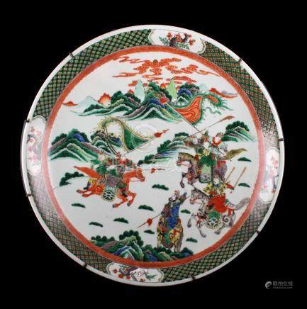 A large Chinese famille verte charger, late 19th / early 20th century, painted with warriors on