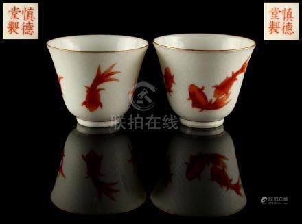 A pair of Chinese iron red decorated sgraffito ground cups, painted with iron red carp fish on